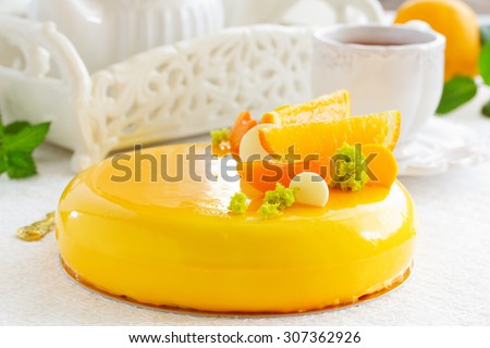 Cake with orange mousse and almond krokantom in the mirror glaze. Selective focus.