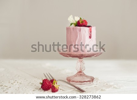 Cake with pink cream and raspberries on wooden background - stock photo