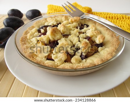 Cake with plums and crumbs - stock photo