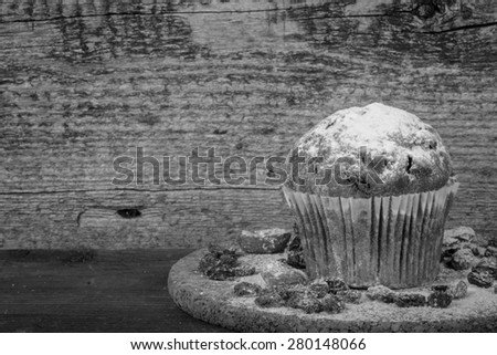 Cake with raisin, dry apricot and sugar powder on the wooden table. Selective focus. Toned. - stock photo