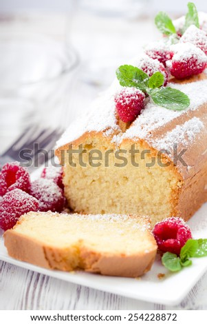 Cake with raspberries and mint leaves, sprinkled with powdered sugar