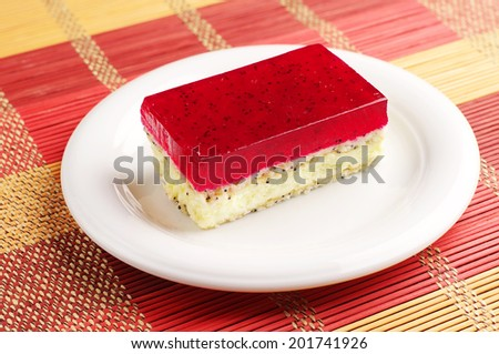 Cake with strawberry jelly and poppy in a plate on colorful bamboo napkin