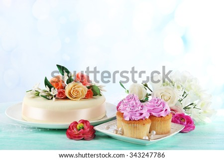Cake with sugar paste flowers and cupcakes, on light background - stock photo