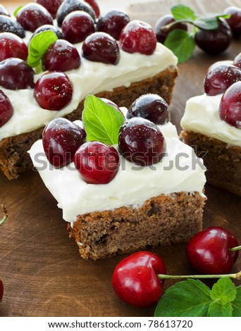 Cake with sweet cherries and whipped sour cream. Shallow dof. - stock photo