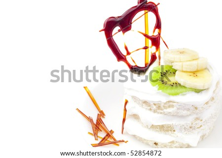 cake with whipped cream, kiwi fruit and caramel isolated on white