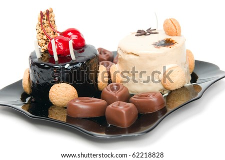 Cake with white and dark chocolate and chocolates on the black plate isolated on a white background. - stock photo
