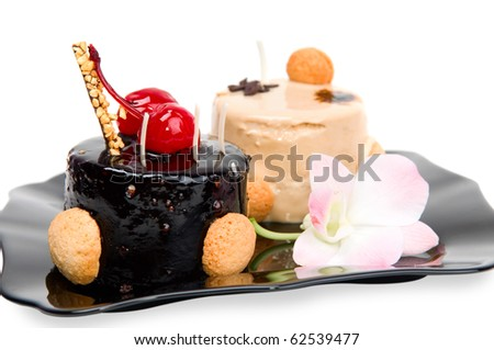 Cake with white and dark chocolate on the black plate isolated on a white background. - stock photo
