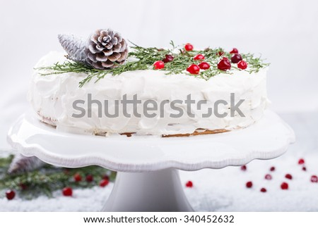 Cake with white cream,garnished with sprigs of spruce ,pine cones,cranberries.