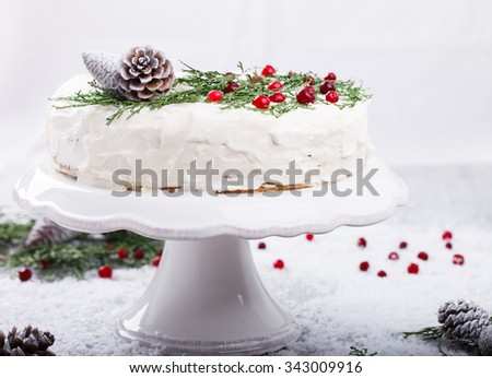Cake with white cream,garnished with sprigs of spruce ,pine cones,cranberries. - stock photo