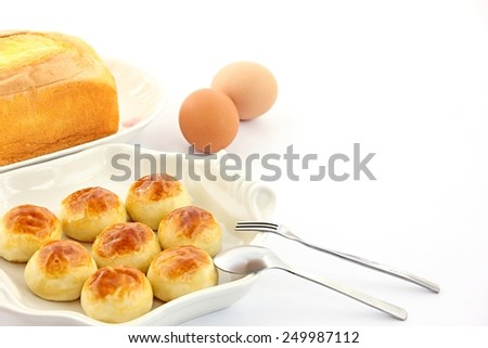 Cakes, eggs, fork and spoon on white background. - stock photo