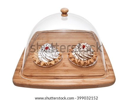 Cakes tarts on a stand with transparent cover - stock photo