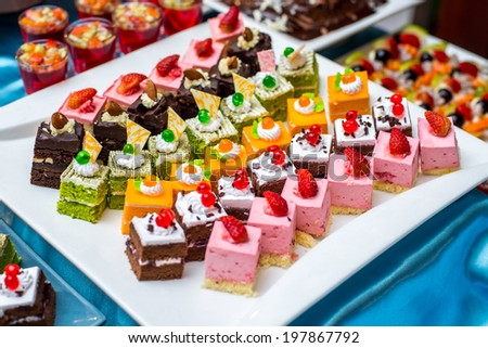 Cakes with different decorations on the plate - stock photo