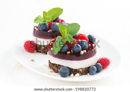 cakes with fruit jelly and fresh berries on a plate, horizontal, close-up - stock photo