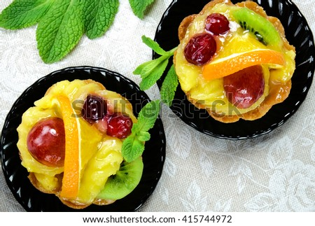 Cakes with slices of fresh fruit orange, kiwi and grapes with jelly and cream on a black saucers on a table cloth. - stock photo