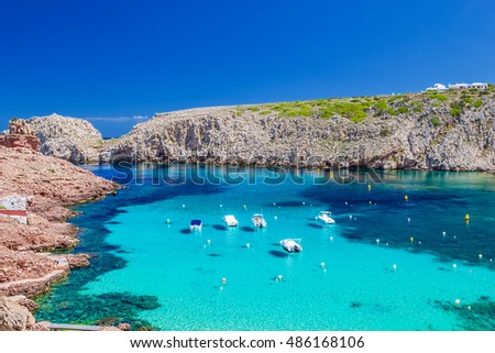 Cala Morell cove with its red rocks and crystal clear blue water, Menorca island, Balearic Islands, Spain.
