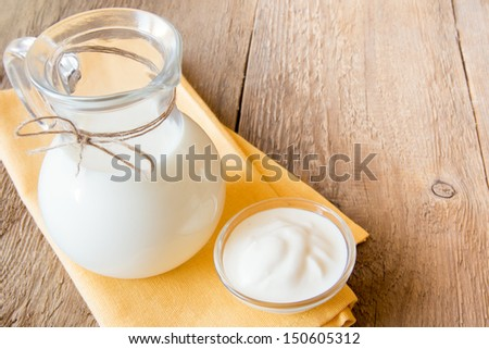 Calcium dairy fresh products: milk and sour cream (yogurt)  on napkin and wooden table, close up, horizontal, copy space - stock photo