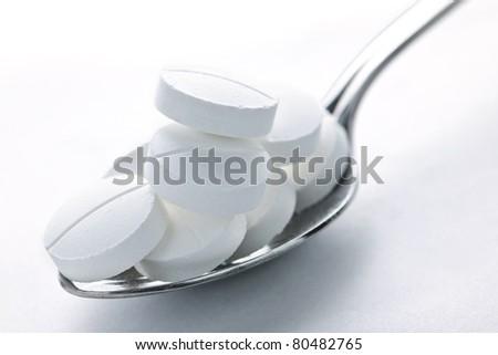 Calcium supplement pills piled on metal spoon closeup - stock photo
