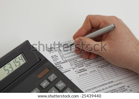 calculating and filling tax form - stock photo