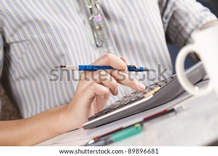 calculating, female model press number on calculator on office table. - stock photo