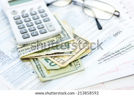 Calculating income tax return with folded cash on a table. - stock photo