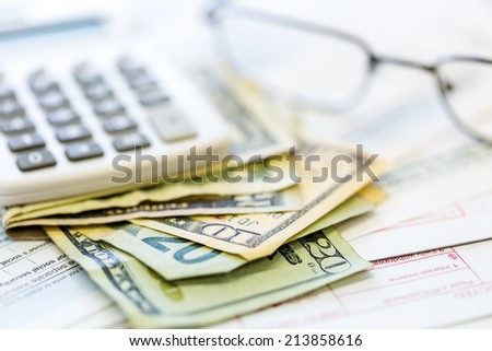 Calculating income tax return with folded cash on a table.