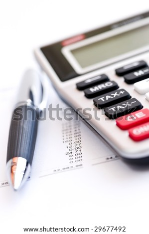 Calculating numbers for income tax return with pen and calculator