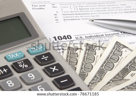 Calculating Tax form 1040 with Calculator and pen