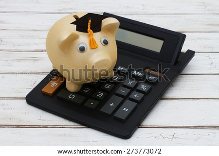 Calculating your education costs, A golden piggy bank with a grad hat on a calculator over a distressed wood background - stock photo