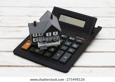 Calculating your mortgage payment, A gray model house on a calculator over a distressed wood background - stock photo
