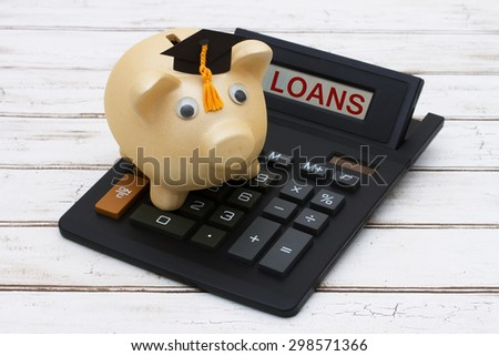Calculating your student loans, A golden piggy bank with a grad hat on a calculator with word loans over a distressed wood background - stock photo