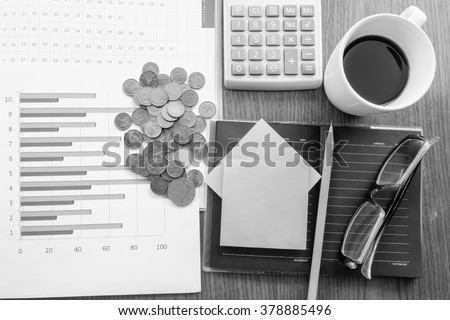 calculator and chart on the wooden table with black and white color concept - stock photo