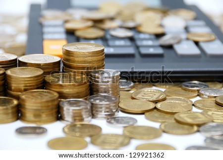 Calculator and different coins close-up - stock photo