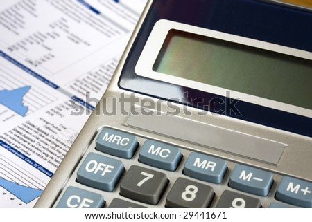 Calculator and financial report as background.Close up