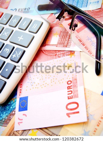 Calculator and glasses for euro banknotes. - stock photo