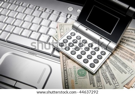 Calculator and Laptop with US Currency with Spot Lighting