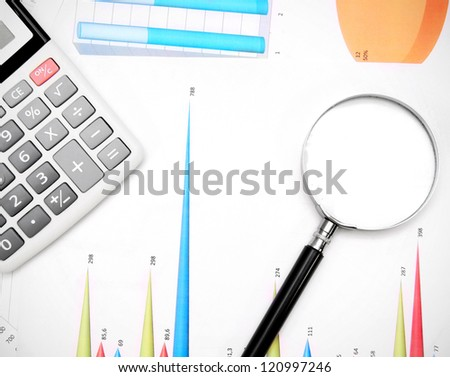 Calculator and magnifier on graphs. - stock photo