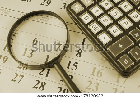 Calculator and magnifying glass on calendar  - stock photo