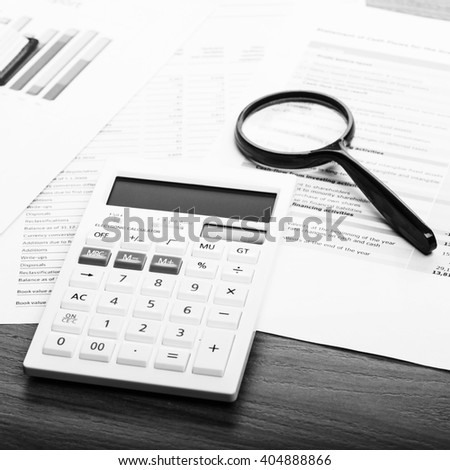 Calculator and magnifying glass on the table  - stock photo