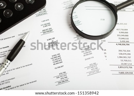 Calculator and magnifying glass over a business document - stock photo
