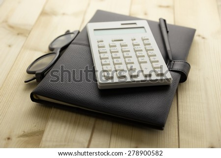 Calculator and Notebook on Desk - stock photo