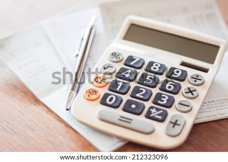 Calculator and pen on bank account passbook, stock photo - stock photo