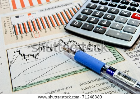 calculator and pen on business newspaper showing chart and graph background