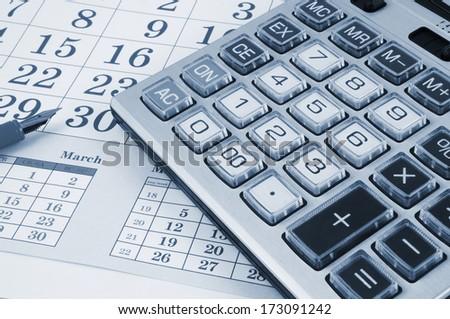 Calculator and pen on calendar background - stock photo