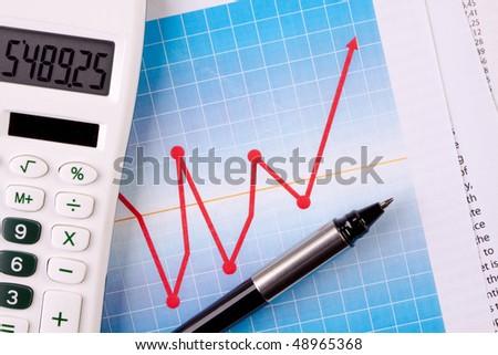 calculator and pen on diagrams - stock photo
