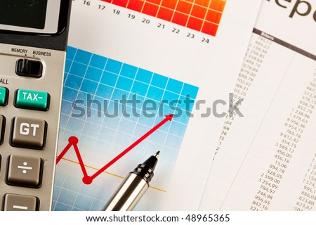 Calculator and pen on graphs - stock photo