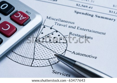 Calculator and pen on monthly spending report with a pie chart. - stock photo