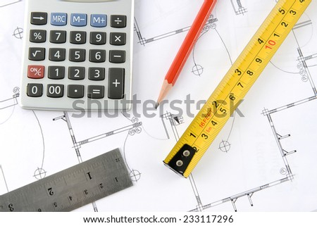 calculator and pencil and measuring tape and ruler on plans - stock photo
