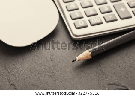 Calculator and pencil. Office equipment at workplace. Conceptual image of desk work, financial paperwork and business economy. - stock photo