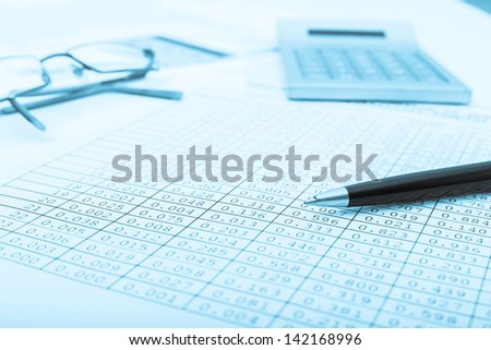 Calculator and the financial report blue toned.Financial accounting.