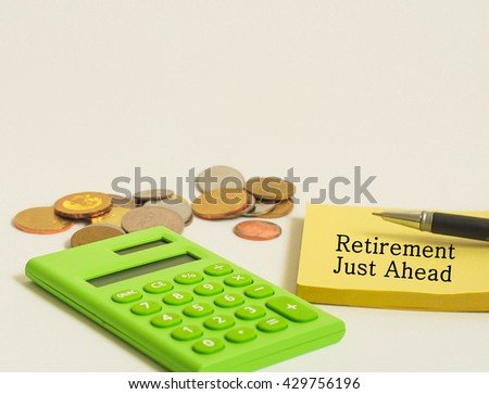 Calculator,coins and yellow note with word retirement  just ahead - stock photo